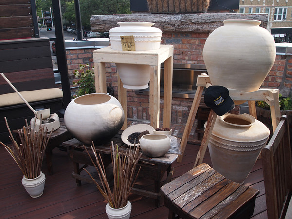 A collection of Sumerian pots and spices on display atop the roof at Fountainhead Chicago